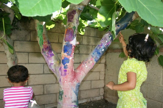 Sisters painting a tree