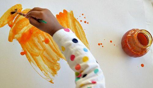 toddler enjoying pumpkin paints
