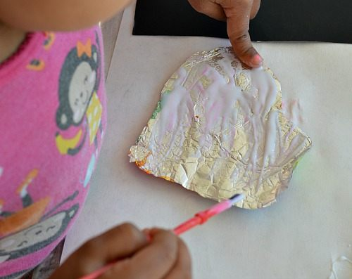 gluing foil hearts to black paper