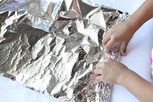 rolling the foil for rainbow craft for kids